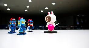 En vit björn med en rosa godis på en mörk teateretapp med ingen berättar robotvakterna som bär blåa hjälmar för att gå ner arkivbilder