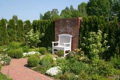 En vit dekorativ bänk vid en tegelstenvägg som omges av en härlig romantisk trädgård arkivbild