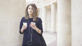 En vit flicka för brunett lyssnar till musik utomhus Royaltyfri Fotografi