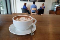 En vit kopp av den härliga varma vita anmärkningen för kakao och för mellanrum på woode Arkivbilder