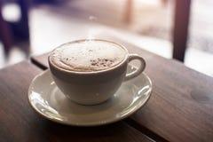 En vit kopp av varmt kaffe på trätabellen med att ånga Royaltyfri Fotografi