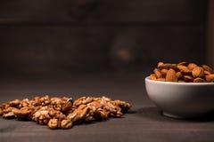 En vit kopp fyllde med mandlar och spridde valnötter på en tabell Arkivfoto