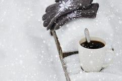 En vit kopp kaffe och stack gråa handskar med en modell på en träbänk i snön under ett snöfall cozy royaltyfria foton