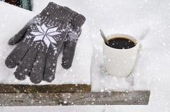 En vit kopp kaffe och stack gråa handskar med en modell på en träbänk i snön under ett snöfall cozy arkivfoton