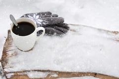 En vit kopp kaffe och stack gråa handskar med en modell på en träbänk i snön under ett snöfall cozy arkivfoto