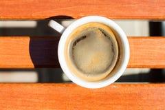 En vit kuper av kaffe på det trä bordlägger Royaltyfria Bilder