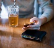 En vit kvinnlig satt dricka ner ingef?rsdrickastund p? hennes mobiltelefon i en ljus milj? arkivfoton