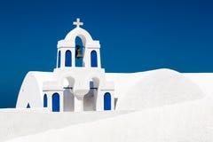 En vit kyrka med blåa beståndsdelar i Oia på den Santorini ön, Grekland Arkivbilder