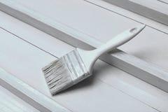 En vit målarpensel på en vit träyttersida royaltyfri bild
