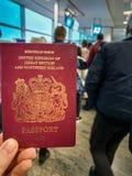 En vit man rymmer hans r?da brittiska pass i hans hand i mitt av en fullsatt avvikelseterminal royaltyfria foton