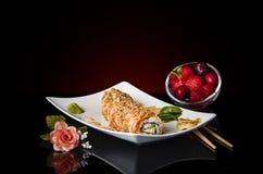 En vit platta med japanska sushirullar med en bunke av frukter Sushibegrepp Royaltyfria Foton