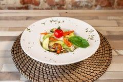 En vit platta med ris och nya grönsaker royaltyfria foton