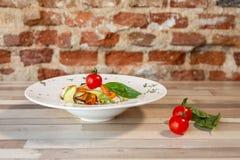 En vit platta med ris och nya grönsaker Ny mat för strikt vegetarian Garnering med oreganon och körsbärsröda tomater royaltyfri foto
