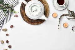 En vit porslintekanna på ett träbräde och en vit kopp med te på en tabell Top beskådar kopiera avstånd arkivbild