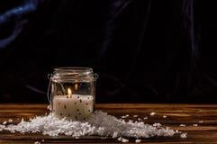 En vit stearinljus i en genomskinlig exponeringsglaskrus bränner, konstgjorda snöflingor läggas ut runt om den royaltyfri foto