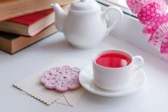 En vit tekopp med rosa parfymerat te och tefatet sitter på en vit bakgrund med färgglad pappers- bunting och inre detaljer, royaltyfri fotografi