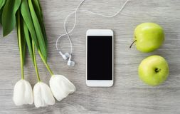 En vit telefon med vit hörlurar, vita tulpan och gröna äpplelögner på en vit trätabell arkivfoto