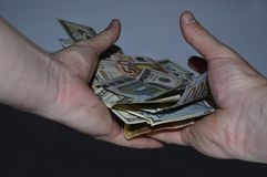 En vriden packe av 100 dollar- och euroräkningar i en hand på en svart bakgrund Arkivfoton