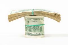 En vriden packe av 100 dollarräkningar står på packar av dollar Arkivbild