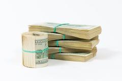En vriden packe av 100 dollarräkningar står på packar av dollar Arkivfoton