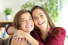 En vrienden of zusters die glimlachen stellen Stock Foto