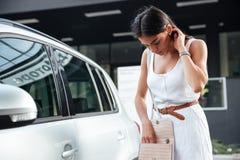 En vrouw die sleutels van auto in zak zich in openlucht bevinden kijken stock afbeeldingen