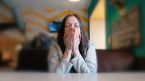 En vrouw die uitrekken zich geeuwen Droevige vrouwenzitting in een koffie en wachten haar orde close-up stock video