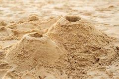 En vulkan som göras av sand på stranden arkivfoton