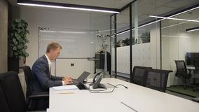 En vuxen affärsman som bara i regeringsställning arbetar på hans skrivbord med bärbara datorn lager videofilmer