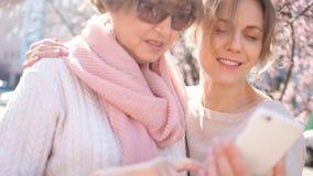 En vuxen dotter och hennes mogna moder står i mitt av gatan som rymmer en smartphone i deras händer stock video