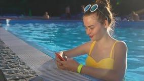 En vuxen flicka som i pölställefotona på sociala nätverk på telefonen stock video