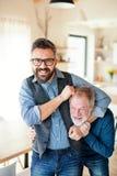 En vuxen hipsterson och en h?g fader inomhus hemma och att ha gyckel arkivfoto