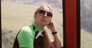 En vuxen kvinna i solglasögon sitter i kabinen av kabelbilen arkivfilmer