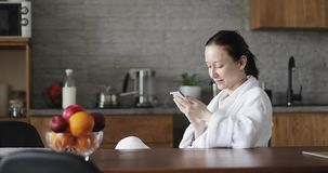 En vuxen kvinna i en vit badrock skriver ett meddelande på en mobiltelefon stock video