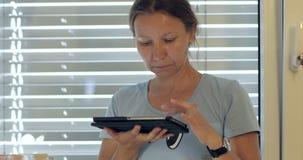 En vuxen kvinna rymmer en minnestavla stock video