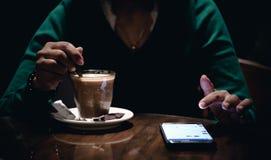 En vuxen kvinnlig som använder hennes telefon och dricker kaffe i ett mörkt rum arkivbilder
