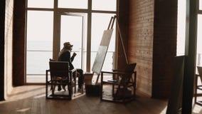 En vuxen målare är förlovad i teckningsmålarfärger på en stor kanfas i hans seminarium arkivfilmer
