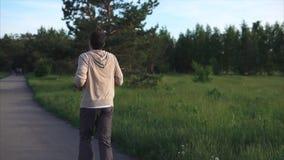 En vuxen man i en sportdräkt kör längs en gå bana parkerar in på en sommardag stock video