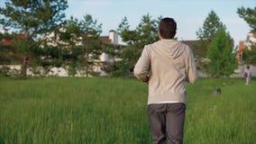 En vuxen man i en sportdräkt kör längs en gå bana parkerar in på en sommardag lager videofilmer
