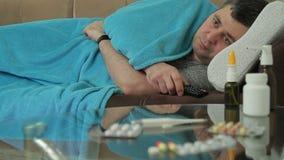 En vuxen man med kalla symptomlögner som slås in i en filt på soffan och strömbrytareTV-kanal av en fjärrkontroll lager videofilmer