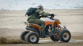 En vuxen man utför ett trick på en ridning för sportkvadratcykel på en sandig strand, en person klarar av professionellt en ytter lager videofilmer