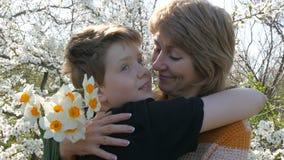 En vuxen medelålders moder kramar och kysser hennes son för tonåring` s ömt mot bakgrunden av ett härligt frodigt lager videofilmer