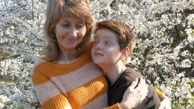 En vuxen medelålders moder kramar och kysser hennes son för tonåring` s ömt mot bakgrunden av ett härligt frodigt stock video