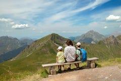 En vuxen person och två pojkar vilar i berg royaltyfria bilder