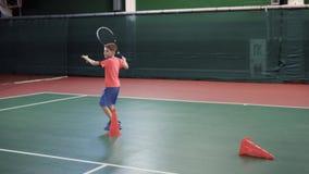 En vuxen pojke lär att spela tennis, en grabb i bollar för tennis för sportklädertakter med en racket, honom kör runt om litet lager videofilmer