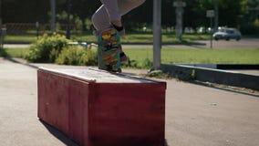 En vuxen skateboarder, som älskar hans hobby, hoppar på en fanbox, då flyttar sig av den på ett bräde i en gataskatepark i lager videofilmer