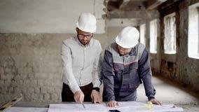 En vuxen tekniker förklarar till arbetaren ett nybyggnadplan, som planlades av arkitekten, folk är i stock video