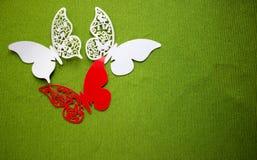 En vykort med fjärilar som isoleras på grön bakgrund Vit och röd fjäril för hantverk royaltyfria foton