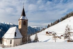 En wintertime beskådar av en liten kyrka med en högväxt kyrktorn Arkivfoto