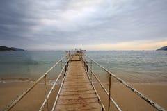 En wood bro på havet Arkivfoto